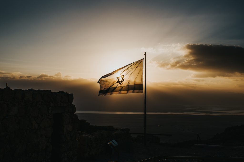 Die israelische Flagge mit dem Davidsstern zwischen zwei waagerechten blauen Balken gegen den Sonnenuntergang fotografiert.